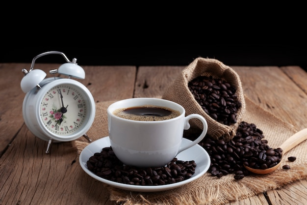 White coffee cup with white alarm clock and coffee beans on old wood plank background