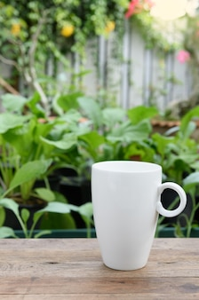 White coffee cup on wood plank in vegetable farm and flowers garden
