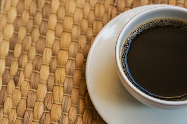 ホワイトコーヒーカップはフロアマットの上に置かれます。