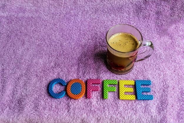 紫色の布の背景とカラフルなコルク素材とガラスの白いコーヒー