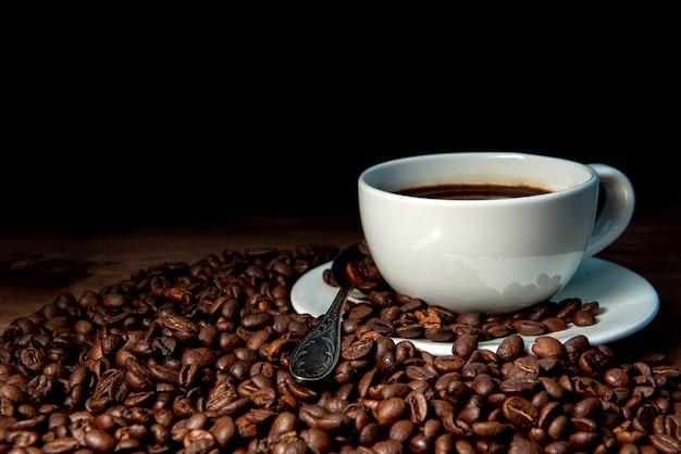 Белая кофейная кружка и кофейные зерна на темном деревянном фоне