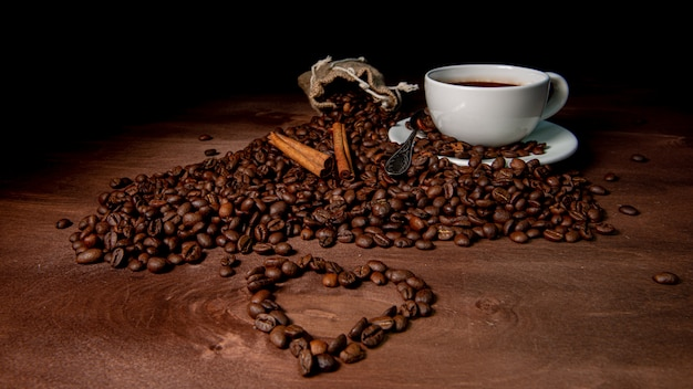 Белая кофейная кружка, палочки корицы и кофейные зерна на темном деревянном фоне, форма сердца из кофейных зерен на переднем плане