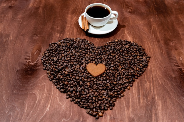 White coffee mug, gingerbread and coffee bean heart on a wooden texture board