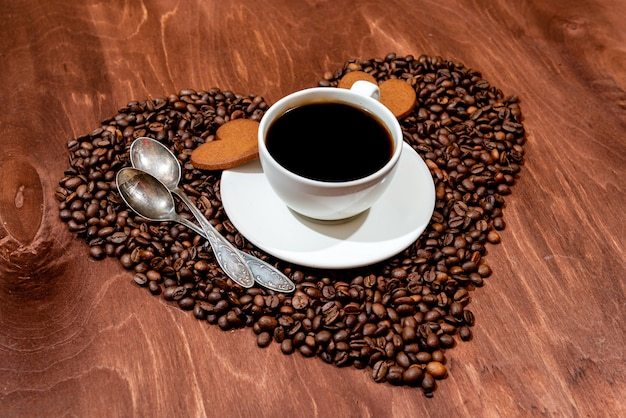 White coffee mug, heart shaped gingerbread and two spoons on a heart shaped base made from coffee beans