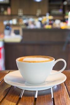 흰색 커피 머그는 커피숍의 나무 테이블에 놓여 있습니다.