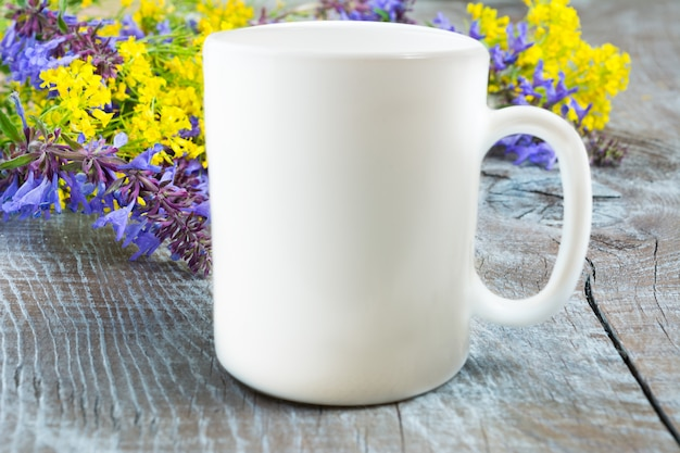 White coffee mug mockup with lilac and yellow flowers
