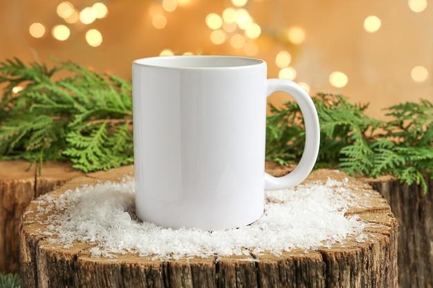 広告のための雪のコピースペースのモックアップと木製のクリスマスの背景に白いコーヒーマグ