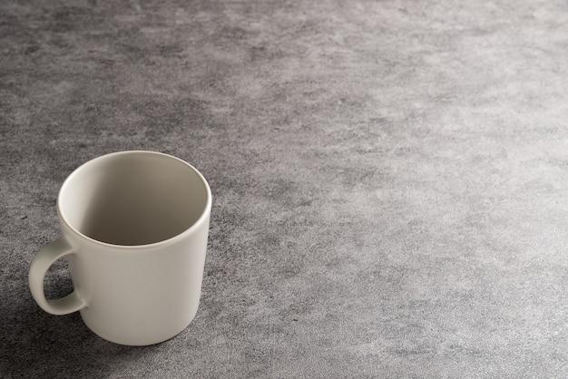 コピースペースと灰色の石の背景に白いコーヒーマグ。