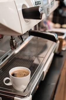 Белая кофейная кружка на столе внутри кафе