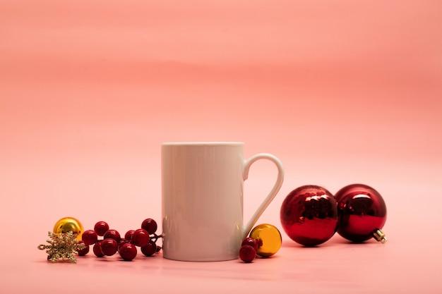Белая кофейная кружка с рождественскими украшениями вокруг нее на розовом фоне
