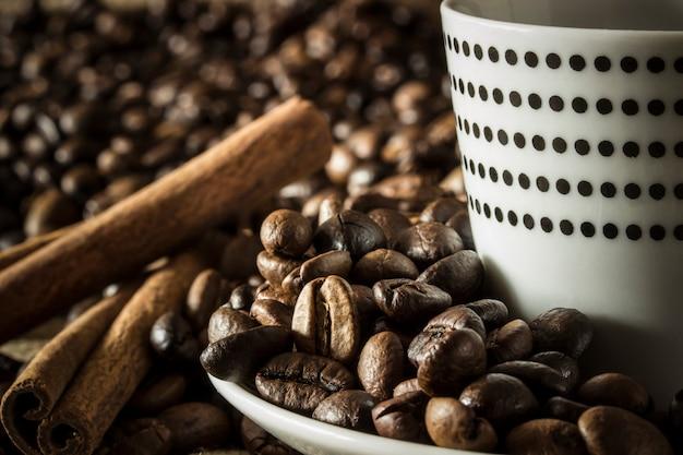 커피 원두와 계피 스틱이있는 물방울 무늬가있는 흰색 커피 머그잔