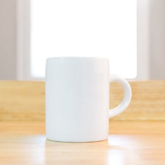 White coffee mug on wooden background in morning environment.