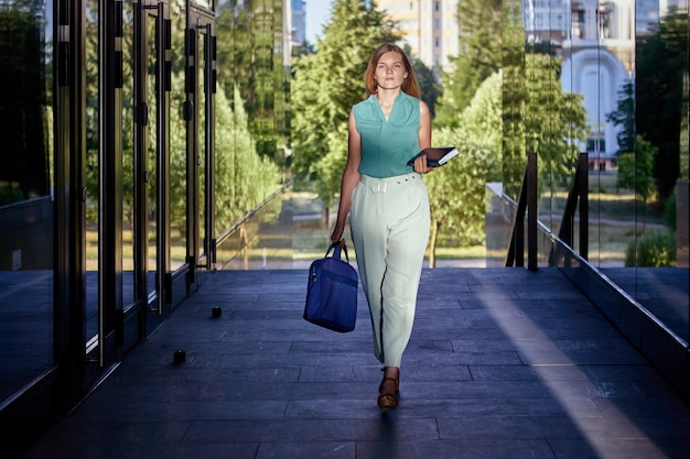 White collar walks near business center with bag for work