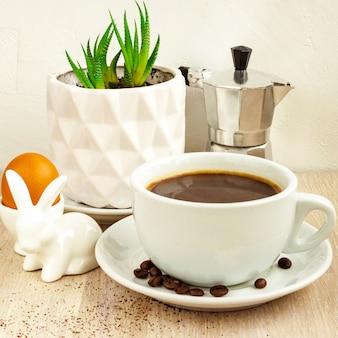 ソーサーと豆、アルミニウムコーヒーメーカー、ベージュの木製テーブルの上の白い鍋に緑の多肉植物とブラックコーヒーの白い色のカップ。イースターウサギの卵ホルダー。セレクティブフォーカス。コピースペース