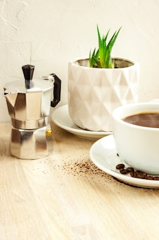 ソーサーと豆、アルミニウムコーヒーメーカー、ベージュの木製テーブルの上の白い鍋に緑の多肉植物とブラックコーヒーの白い色のカップ。セレクティブフォーカス。コピースペース