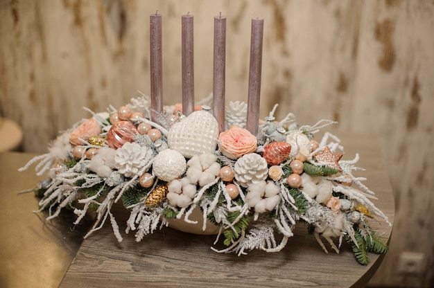 White color vase with christmas decor composition of fir-tree branches, candles, flowers and ornaments on the table
