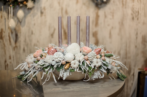 White color vase with christmas decor composition of fir-tree branches, candles, flowers and ornaments