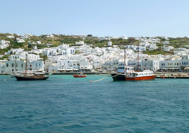 White colored greek islands architecture on the hillside with boats at mykonos old port, greece