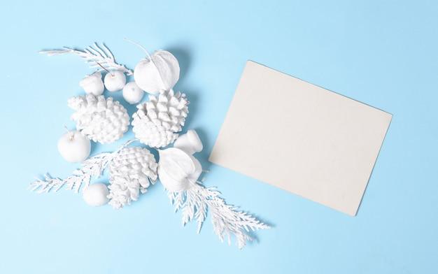 Белые сосновые шишки, ветки, цветы физалиса и пустая подарочная карта. плоская планировка минимальная концепция. белые объекты на синем фоне.