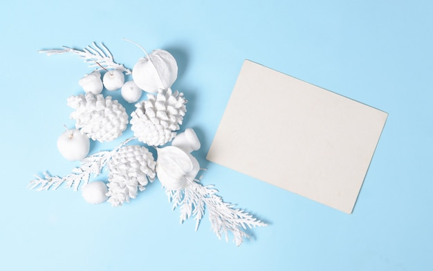 White colored pine cones, branches, physalis flowers and with empty gift card. flat lay minimal concept. white objects on a blue background.