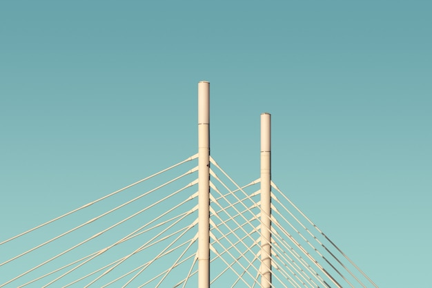 White columns and cables of a bridge with the blue sky in the background