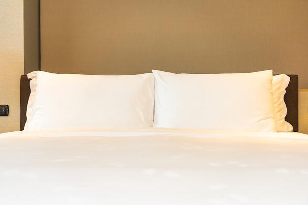 Белая удобная подушка и одеяло на кровати с легкой лампой