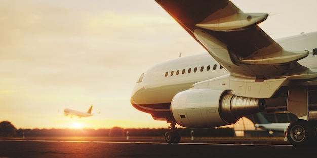 日没時に空港の滑走路に立っている白い民間航空機
