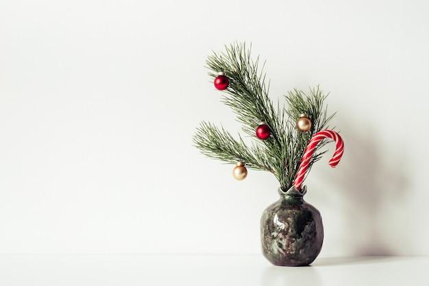꽃병에 작은 장식된 크리스마스 트리가 있는 흰색 구성. 텍스트 또는 글자를 위한 공간을 복사합니다.