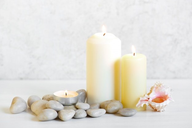 White composition with three burning candles and stones