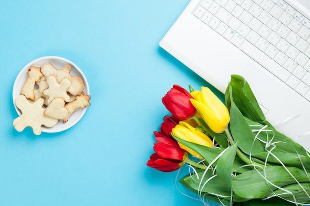 Белый компьютер и букет тюльпанов с печеньем на синем фоне