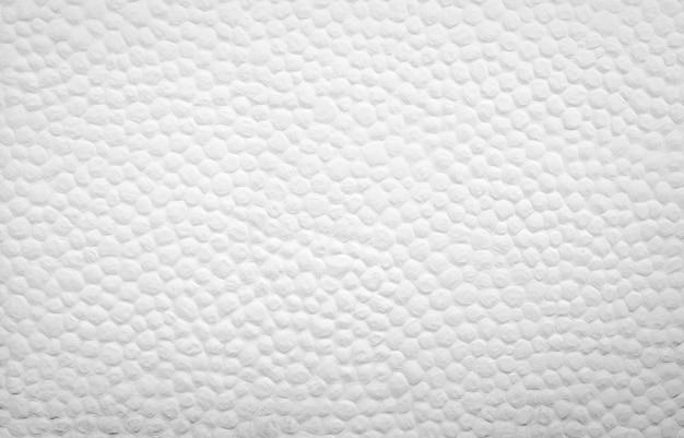 小さな丸い凸点の白いコンクリートの壁のテクスチャ装飾。建物の白いセメントの壁。アート。外装または内装のコンセプト。空の白い壁。ホームインテリアデザイン。