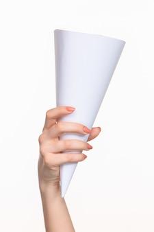 Cono bianco degli oggetti di scena nelle mani femminili su sfondo bianco con ombra a destra