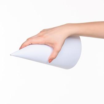 Cono bianco di oggetti di scena in mani femminili su bianco con ombra a destra