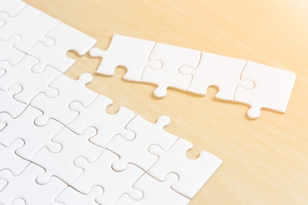 White connected jigsaw puzzle pieces on wooden table