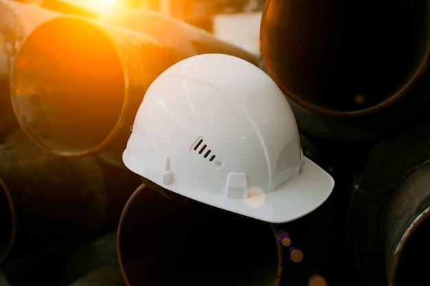 白い建設用ヘルメットがパイプの上に横たわっています