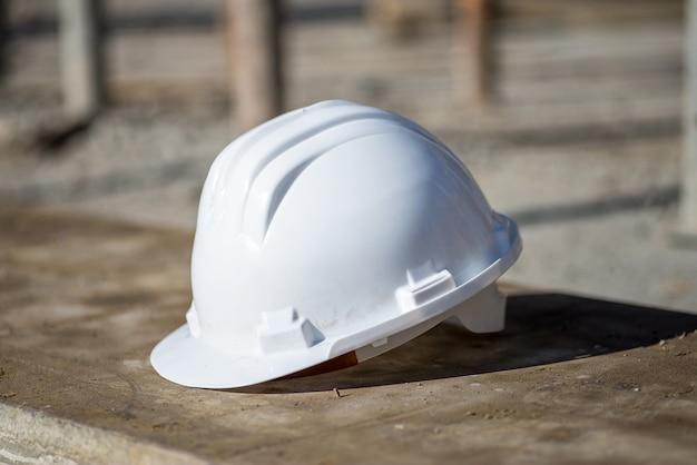 햇빛 아래 지상에 흰색 건설 헬멧