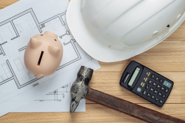 White construction safety helmet and piggy bank with blueprint, hammer, calculator on wooden boards. building idea. house building costs. top view