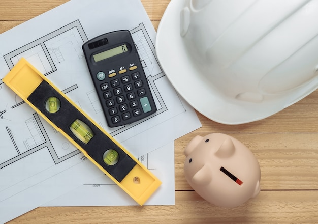 White construction safety helmet and piggy bank with blueprint, level, calculator on wooden boards. building idea. house building costs. top view