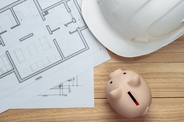White construction safety helmet and piggy bank with blueprint on wooden boards. building idea. house building costs. top view