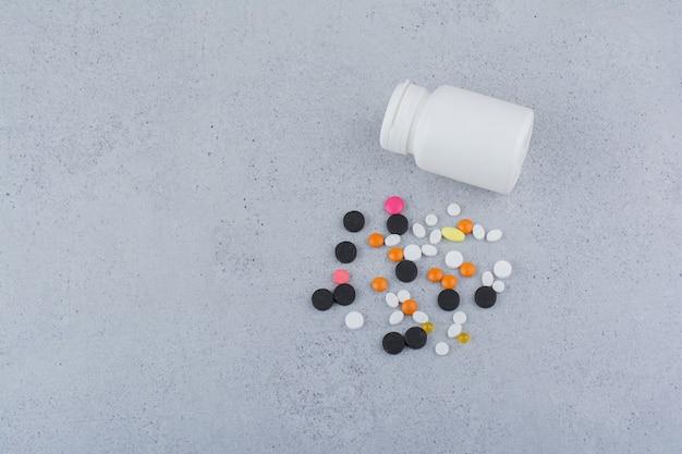 Белый контейнер и куча различных таблеток на мраморной поверхности.