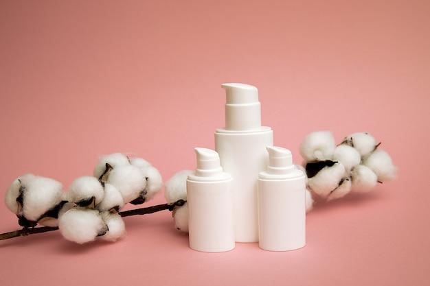 綿の花の化粧品ペットボトル用の白い容器、モックアップブランドの空白のラベル、ナチュラルビューティー製品のコンセプト。ピンクの背景、クローズアップ写真