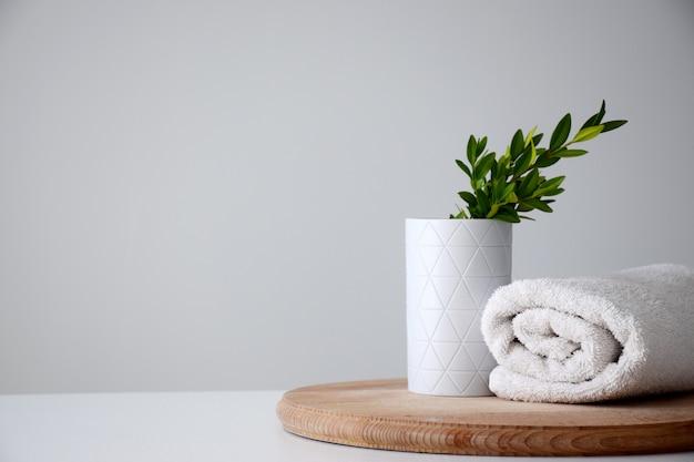 緑のハーブと木の板に白い巻きタオルの白いコンテナー