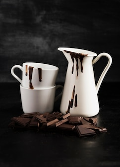 White containers filled with melted chocolate and pieces of chocolate