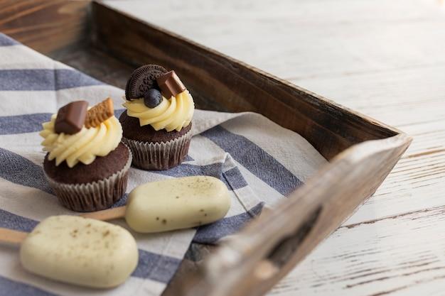 Мороженое из белого печенья на палочке и вкусные кексы и кексы на подносе на деревянном столе. украшают сверху разными конфетами, печеньем и разноцветным сладким сливочным сыром.