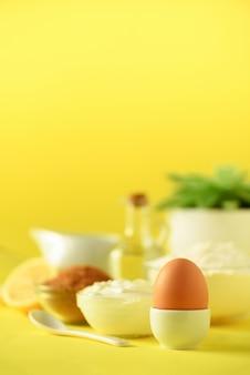 黄色の背景に白の調理器具。食品成分。卵のマクロケーキを調理し、パンを焼くコンセプト。スペースをコピーします。
