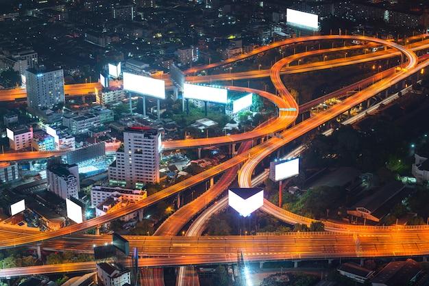 都市のビルボードと高層ビルの空のテンプレート画面による広告ビジネスでのコミュニケーションのための自動車輸送ビルボードを備えた高速道路の横の広告の白いコピースペースの背景