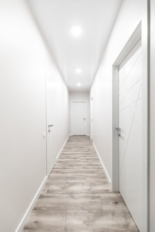 White corridor with white doors in the flat