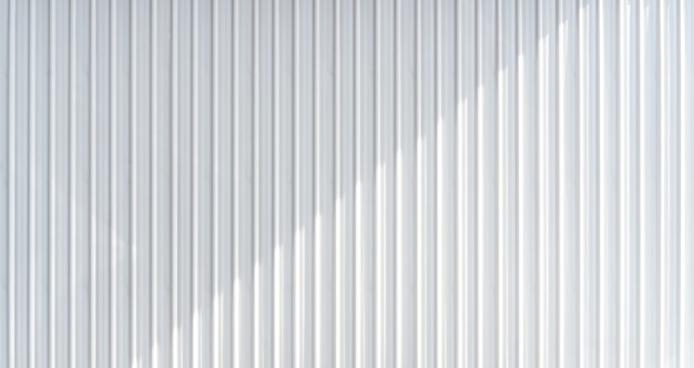 White corrugated metal wall texture with casting shadow.