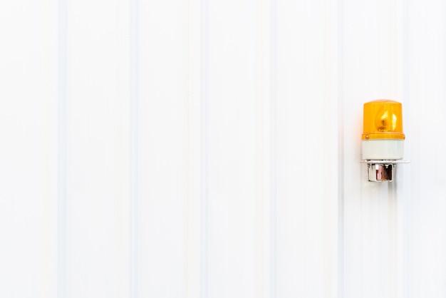 오른쪽에 노란색 비상등이있는 흰색 골판지 금속 벽 텍스처