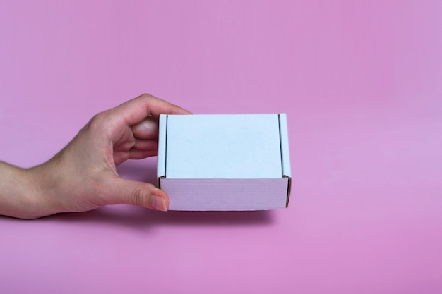 White corton box for mock-up in a female hand on a pink background. space for text